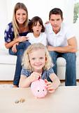 Smiling little girl inserting coin in a piggybank in the living room