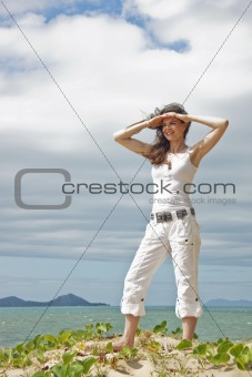 Fit and attractive woman standing looking out over a tropical co