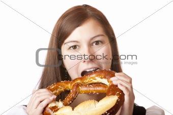 Portrait of woman in Dirndl eating Oktoberfest Pretzel