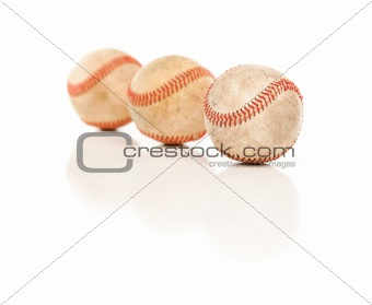 Three Baseballs Isolated on a Reflective White Background.