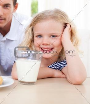 Little blond girl drinking milk in the kitchen