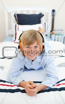 Smiling blond boy listening to music