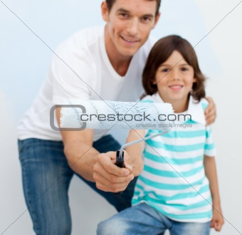 Father and his son holding a paintbrush