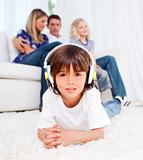 Cute little boy listening music lying on floor