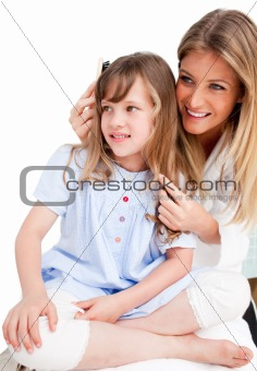 Charming woman brushing her daugther's hair
