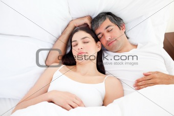 Affectionate couple hugging lying in their bed