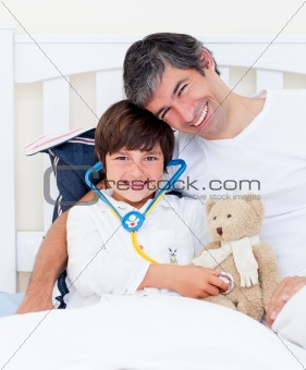 Attentive father and his sick son playing with a stethoscope