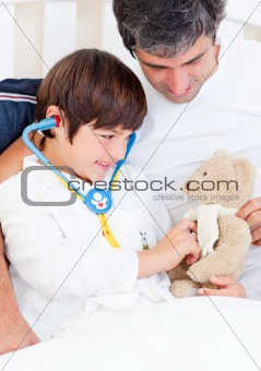 Caring father and his sick son playing with a stethoscope
