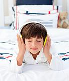 Adorable little boy listening music with headphones on