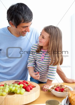 Affectionate father and his daughter having breakfast