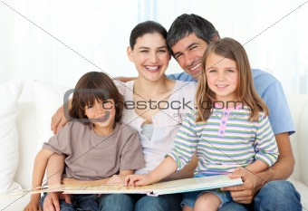 Joyful family reading together on the sofa