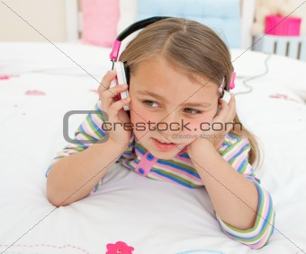 Adorable gril listening to music lying on her bed