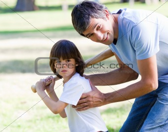 Attentive father playing baseball with his son