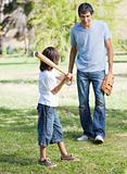 Cute little boy playing baseball with his father