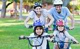 Adorable family riding bikes in a park