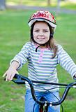 Joyful little girl riding a bike