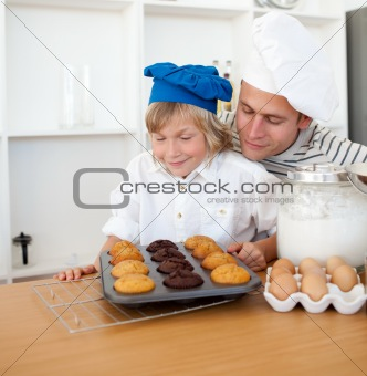 Attentive father and his son presenting their muffins