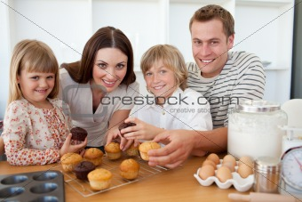 Smiling family eating muffins