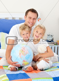Adorable siblings and their father looking at a terrestrial glob