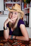 Smiling young blonde woman with cowboy hat in a cafe