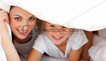 Happy mother and her blond girl playing together on a bed