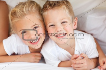 Adorable siblings playing on a bed