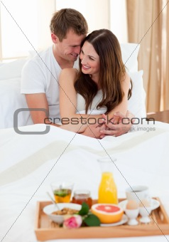 Intimate couple having breakfast lying in bed