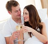 Romantic couple drinking champagne lying in bed