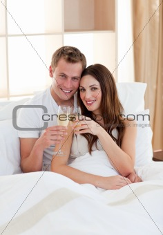 Affectionate couple drinking champagne lying in bed