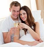 Loving couple drinking champagne lying in bed