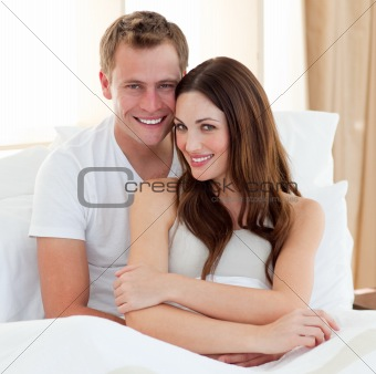 Beautiful lovers embracing lying in bed