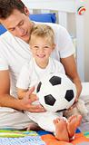Close-up of a little boy and his father playing with a soccer ball sitting on bed