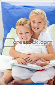 Blond brother and daughter reading books