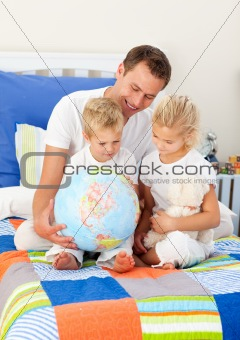 Blond siblings and their father looking at a terrestrial globe