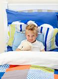 Adorable little boy lying in bed