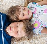 Cute siblings lying on the floor with heads together