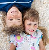 Adorable siblings lying on the floor with heads together