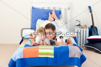Attractive father and his son playing with a soccer ball lying on bed