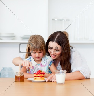 Loving little girl and her mother having breakfast