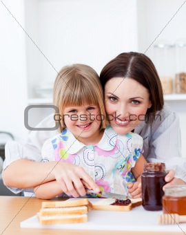 Cute little girl and her mother preparing toasts