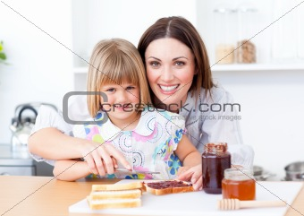 Adorable little girl and her mother preparing toasts in the kitchen