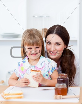 Cute little girl and her mother eating slices of bread