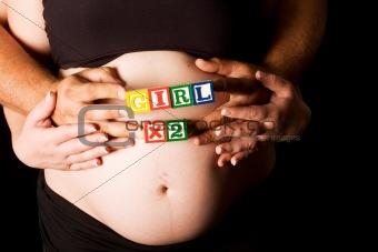 Pregnant couple holding wooden playing blocks