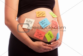 Pregnant Caucasian woman with sticky notes on belly