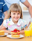 Portrait of a cute little girl having breakfast in the kitchen