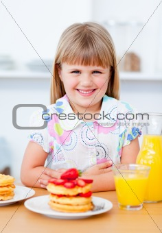 Joyful little girl eating waffles with strawberries