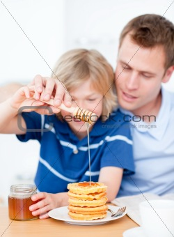 Smiling boy and his father putting honey on waffles