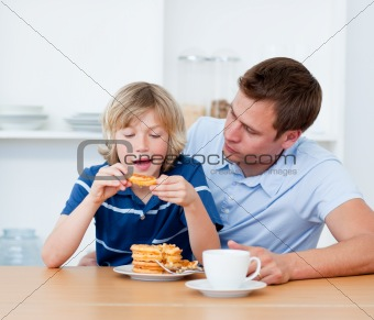 Charming father and his son eating waffles