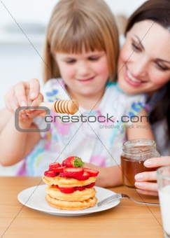 Cute little girl and her mother putting honey on waffles