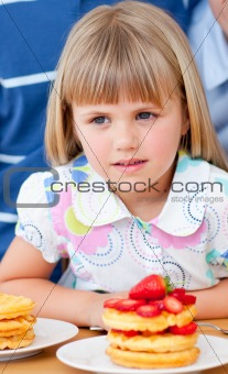 Cute little girl eating waffles with strawberries